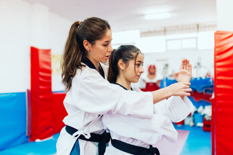 Instructor teaching martial arts to young woman