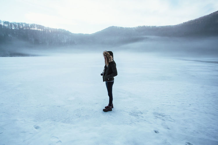 Side view of woman standing on frozen lake against sky