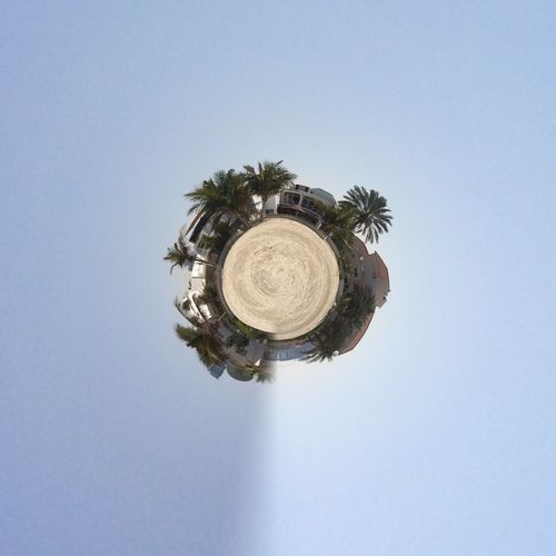 Little planet effect of houses and palm trees at beach against clear sky