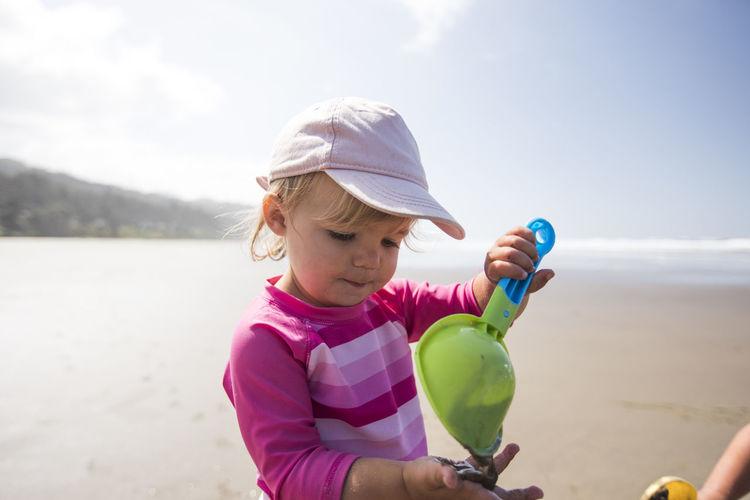 Full length of cute girl holding sunglasses on beach