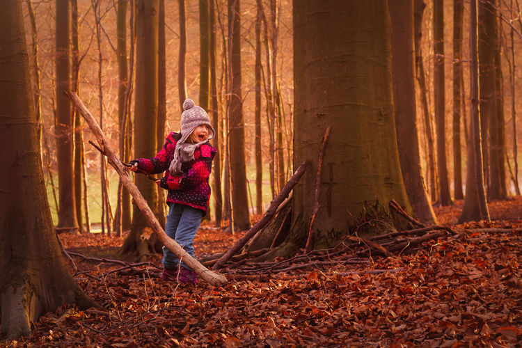 Full Length Of Boy Playing On Field In Forest