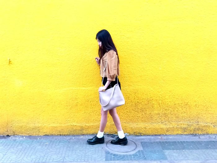 Full length of woman standing on footpath against yellow wall