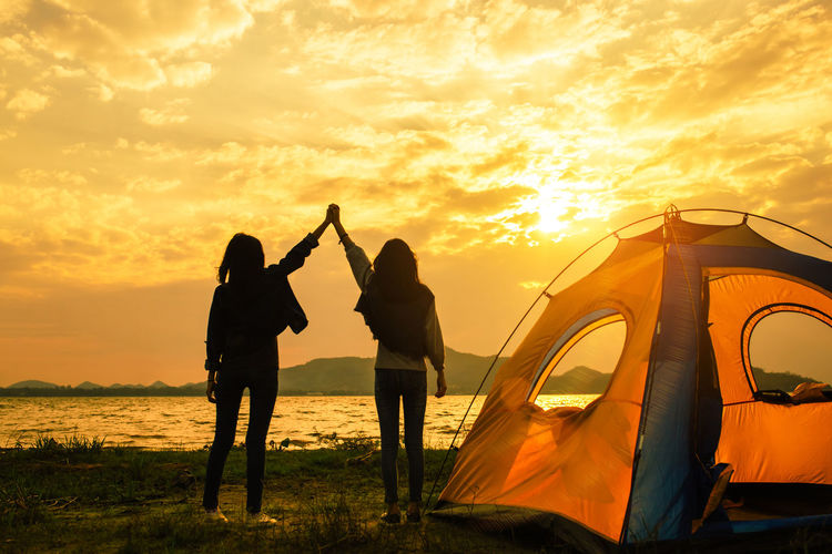 Friendship of young women resting camp near mountain after trekking destination together with tent at sunset. Sunset Two People Sky Leisure Activity Real People Lifestyles Women Men Togetherness Orange Color Mode Of Transportation Bonding Cloud - Sky Transportation Couple - Relationship Adult Beauty In Nature Standing Positive Emotion Love Arms Raised
