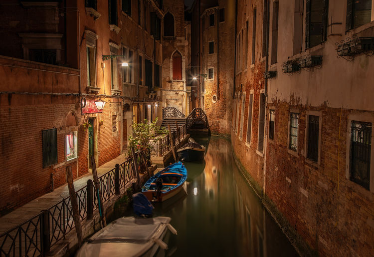 Narrow canal among beautiful old brick houses in Venice Architecture Canal Built Structure Mode Of Transportation Transportation Building Exterior Nautical Vessel Water Night Building City Illuminated Residential District Travel Waterfront Gondola - Traditional Boat Reflection Outdoors Nature Alley Venice, Italy Darkness Reflection Boat Old Vintage Architecture Alleyway Bridge Travel Destinations Travel Tourism Vacations Summer Spring Italy Europe Wall Lamp Landmark Historical Island Narrow Romantic Scenery Urban Town Tranquility Scenic View