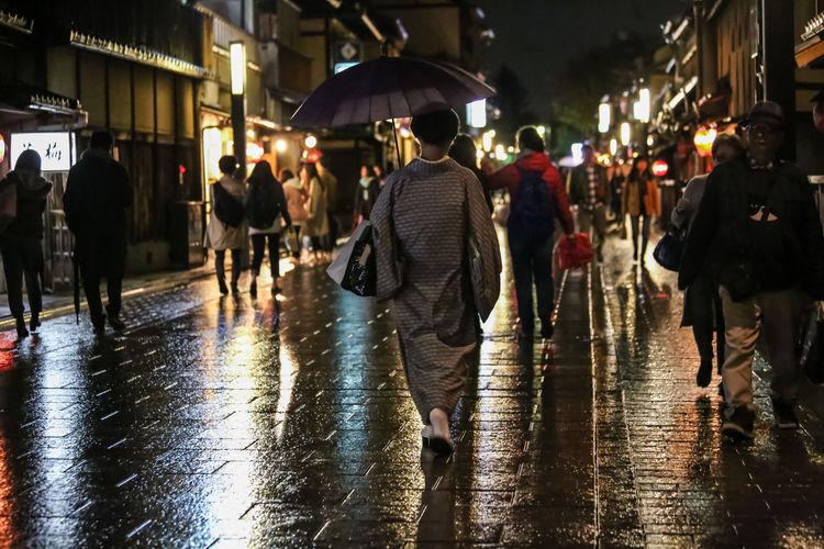 Group of people walking on wet street at night