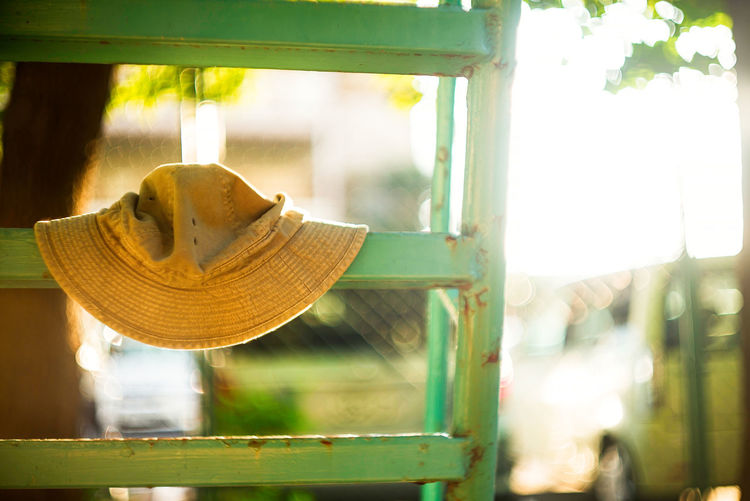 Close-up of yellow hat hanging on window