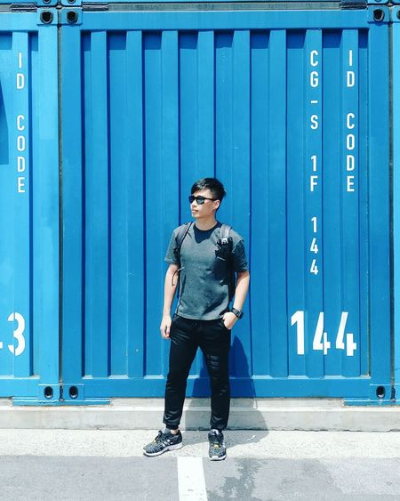 Full length of young man standing against blue wall