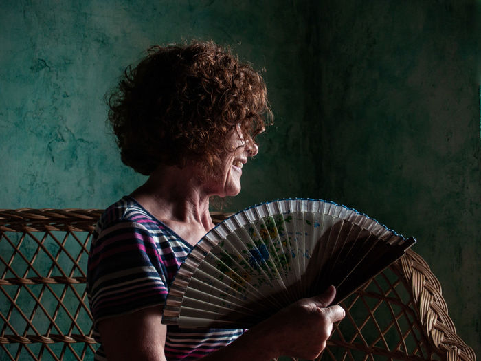Smiling woman holding hand fan at home