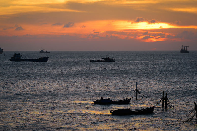 Silhouette boats sailing on sea against cloudy sky during sunset