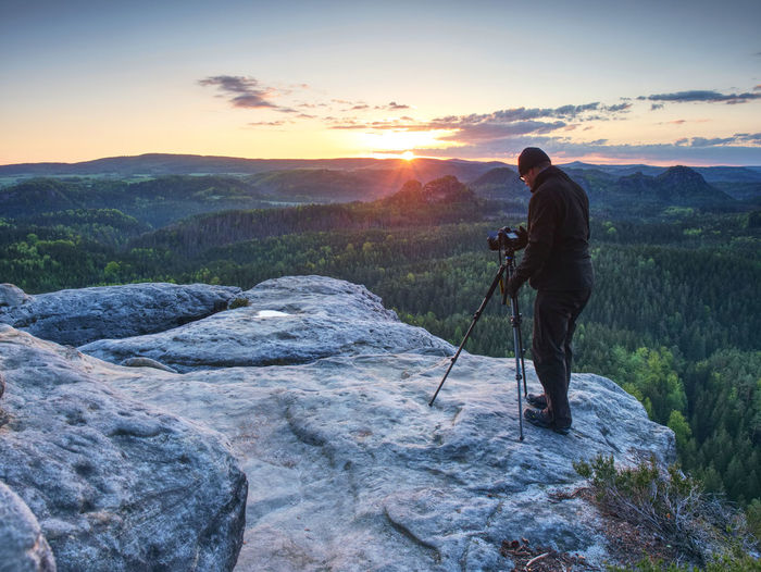 Tall photographer prepare camera for take picture of fall mountains. photograph at colorful valley