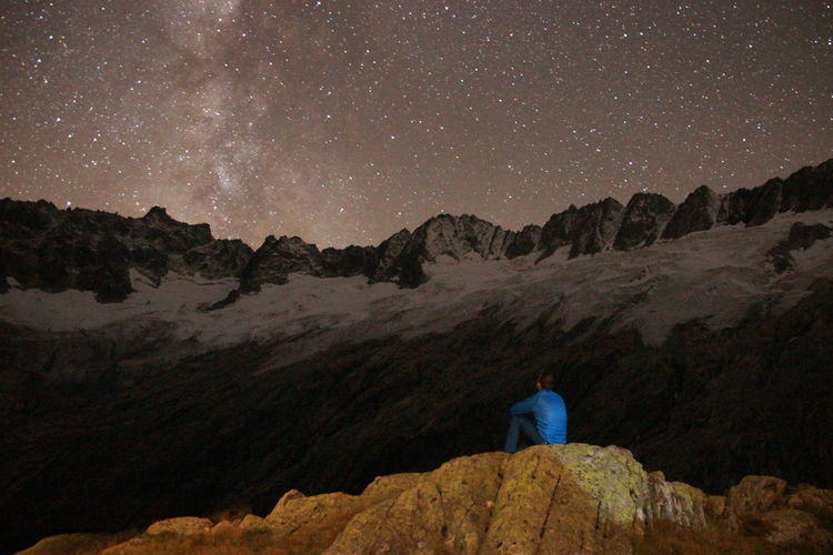 Rear view of man sitting on rock against star field