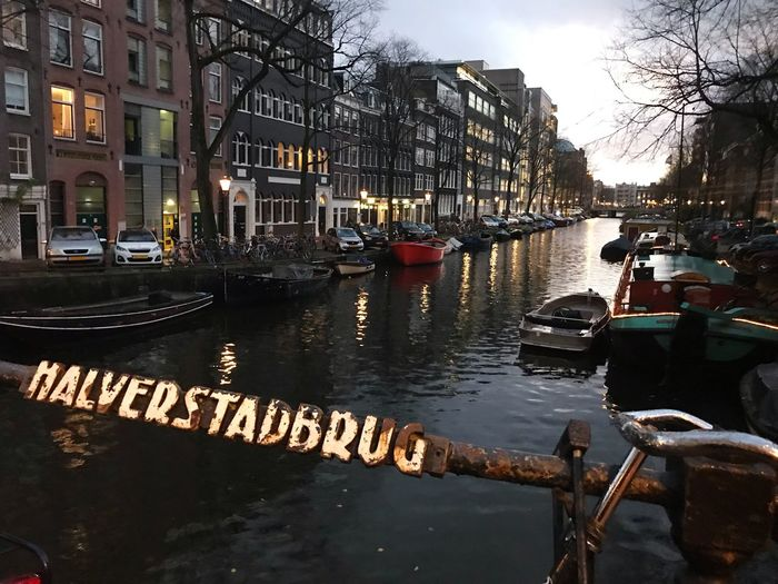 Canal in Amsterdam near Weesperplein and UVA Building Netherlands Amsterdam Building Exterior Architecture Built Structure City Street Nature Canal Nautical Vessel Residential District Outdoors Car Tree First Eyeem Photo
