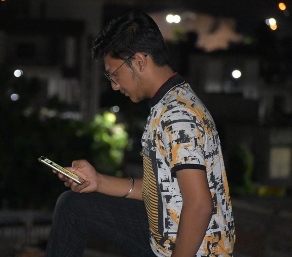 Side view of teenager using mobile phone