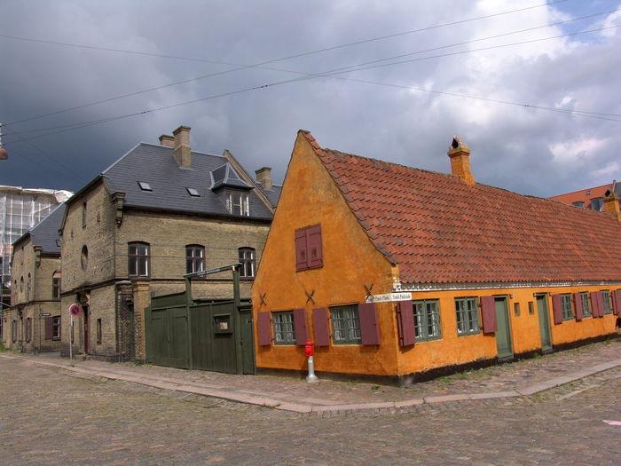Houses on street against cloudy sky