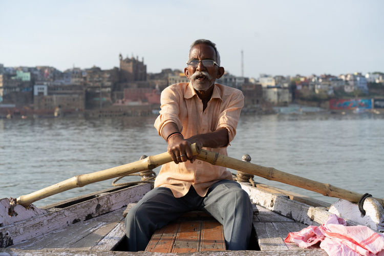 Young man sitting on boat against river