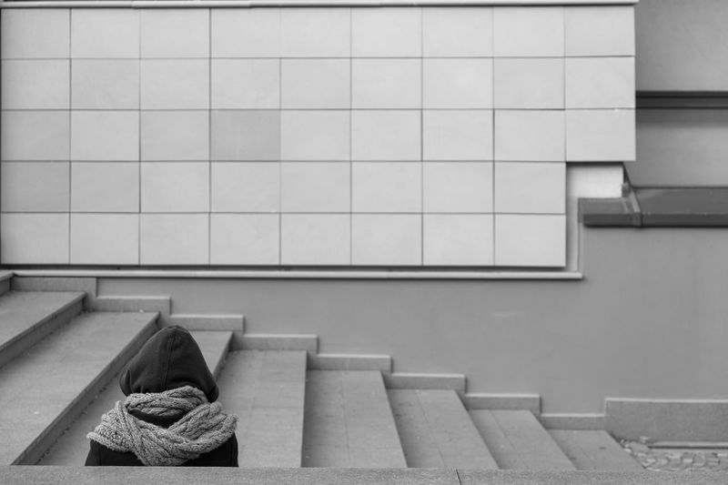 Person Sitting On Steps Against Wall