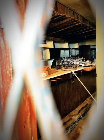 """""""Natural Light"""" Shot through a heavy metal screen on a secured door, an old neon light sits on top of the bar of the long abandoned local watering hole on the Main Street Of The Village of Corona, New Mexico. Story goes that the owner of the bar committed suicide in the basement of the establishment decades ago ending its long run as a popular hangout in the heyday of Corona. Neon Sign Mystery Historical Building Abandoned Bar Bar Indoors  No People Focus On Background Selective Focus"""
