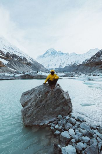 Man Sitting On Rock Amidst River Against Mountains