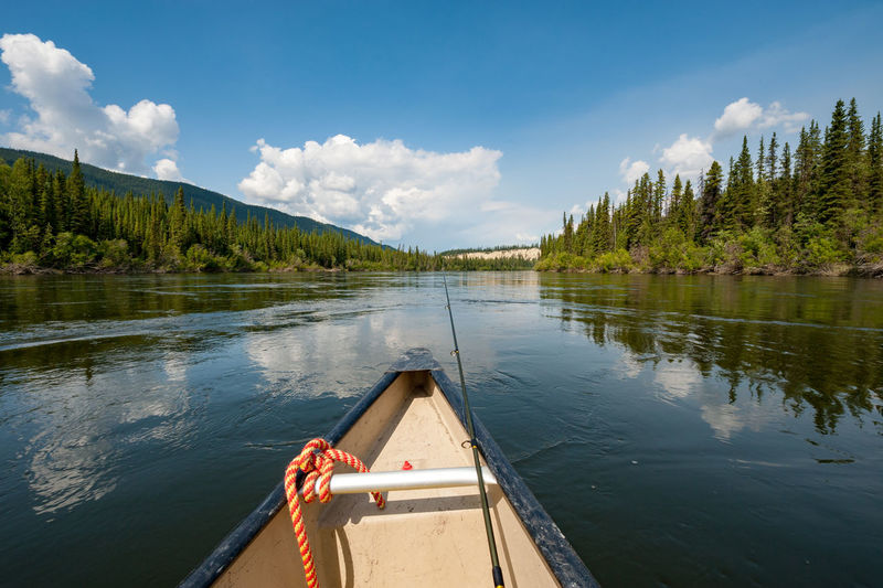 Paddling down Yukon river in Canada Canoe Teslin Yukon Adventure Beauty In Nature Canada Cloud - Sky Day Fishing Forest Nature Paddling Reflection Remote River Rod Scenics Sky Tranquil Scene Tranquility Tree Water Wild Wilderness