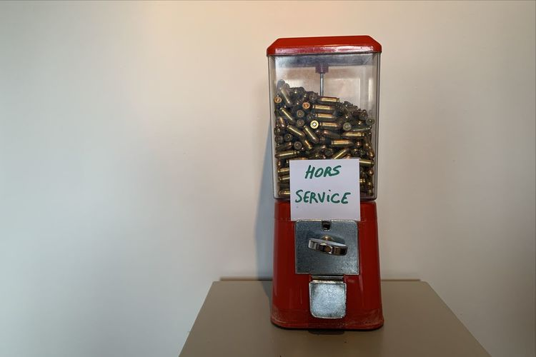 Close-up of bullets in gumball machine on table against wall