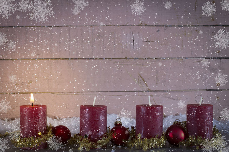 Close-up of christmas decoration on table against wood paneling