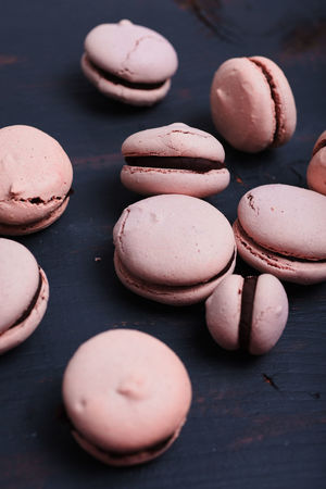 Making homemade French Macarons with raspberry coffee flavor: Close up of imperfect, light pink macarons filled with chocolate ganache on wooden background Chocolate Cookies Macarons Pink Almonds Baking Delicious Food French Cuisine French Macarons Kitchen Light Pink Meringue Pastry Patisserie Raspberry Suga
