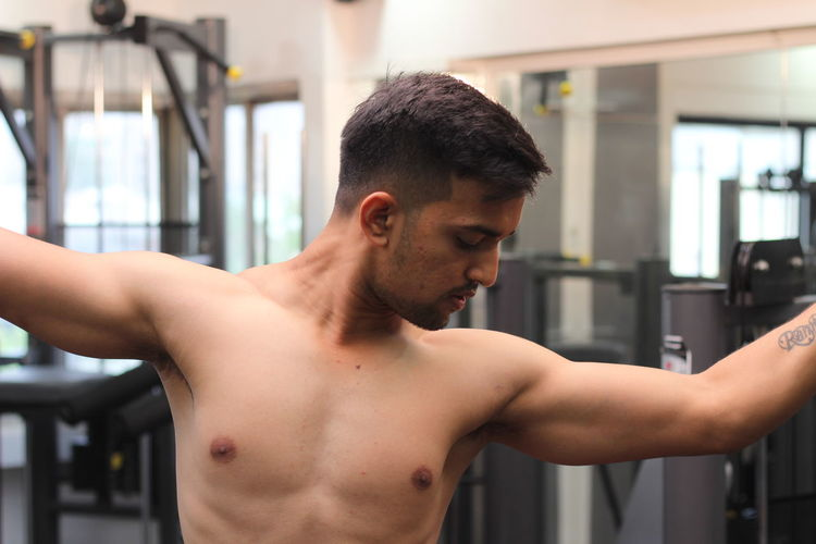 Shirtless young man flexing muscles in gym