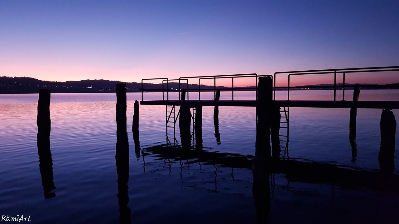 sky, sunset, water, beauty in nature, scenics - nature, tranquil scene, tranquility, silhouette, nature, clear sky, built structure, reflection, lake, architecture, orange color, no people, idyllic, waterfront, outdoors, purple, wooden post