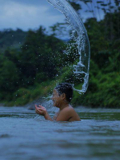 Full length of shirtless man in water