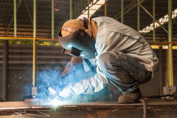 Man working on metal structure in factory