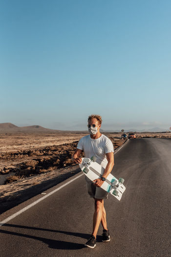 Full length portrait of man standing on road against clear sky