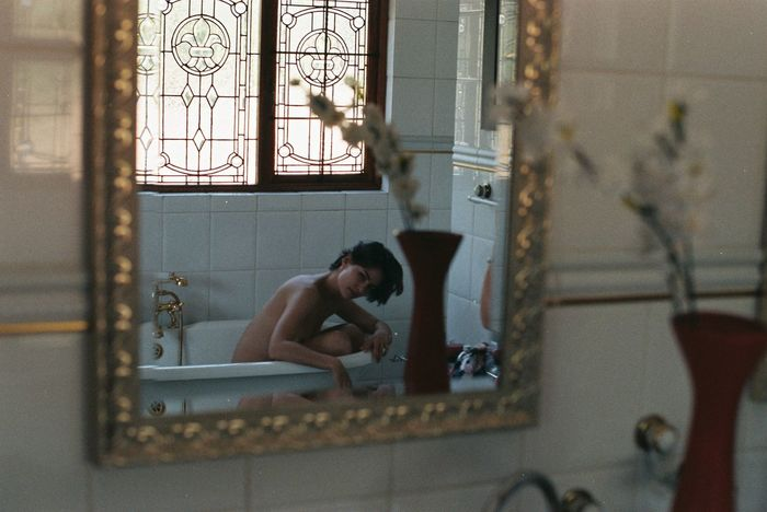 MAN SITTING IN BATHROOM AT HOME