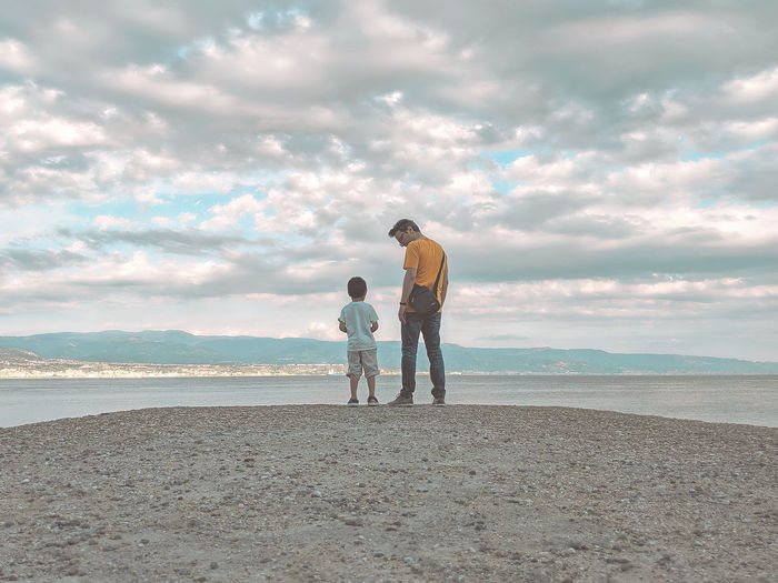 Full length of father and son at standing at beach
