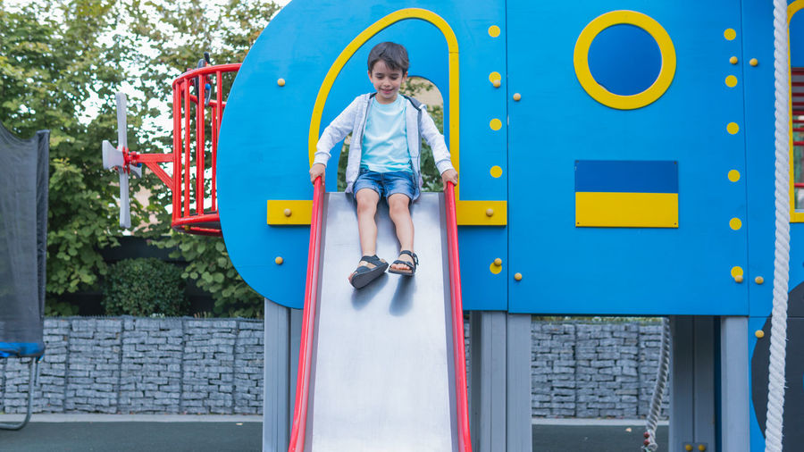 Full length of boy playing on slide in playground