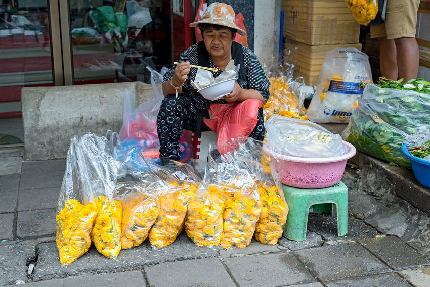 A thai street vendor takes her lunch break from selling large bags of yellow carnations on a Bangkok side street. Asian  Bagged Bangkok Carnations Eating Noodles Street Vendor Thailand Yellow Carnation Adult Chop Sticks Food Food And Drink Freshness Portrait Real People Resting Retail  Smiling