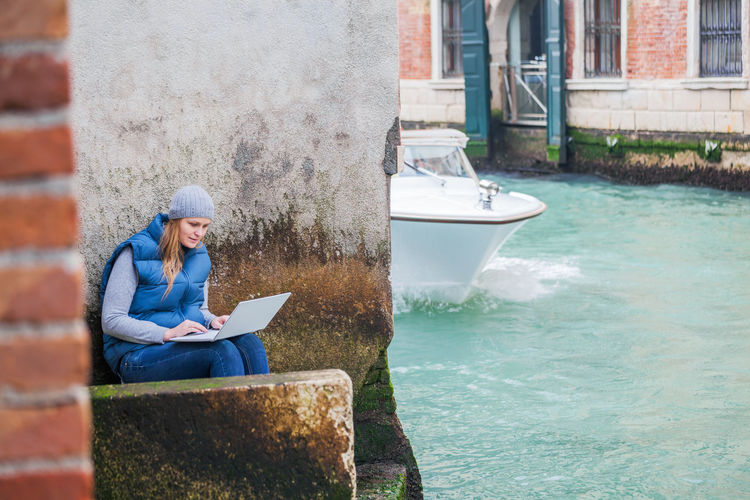 Woman using laptop while sitting on steps by canal