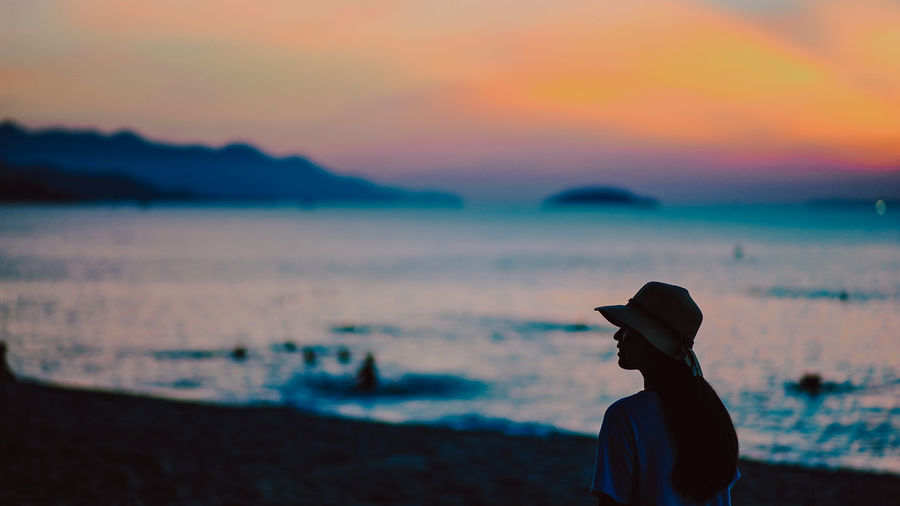 Rear view of silhouette woman standing at beach during sunset