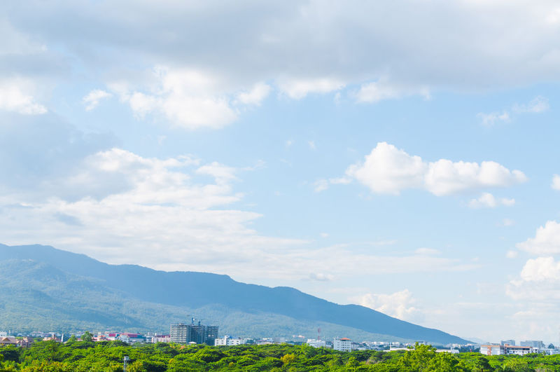 Scenic view of buildings and mountains against sky