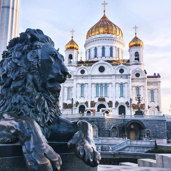 Lion statue by cathedral of christ the saviour against sky