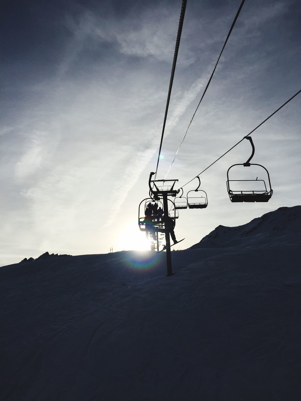 Low Angle View Of Ski Lift Over Snow Covered Mountain Against Sky