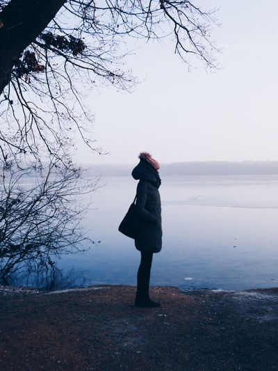 Woman standing on shore against sky