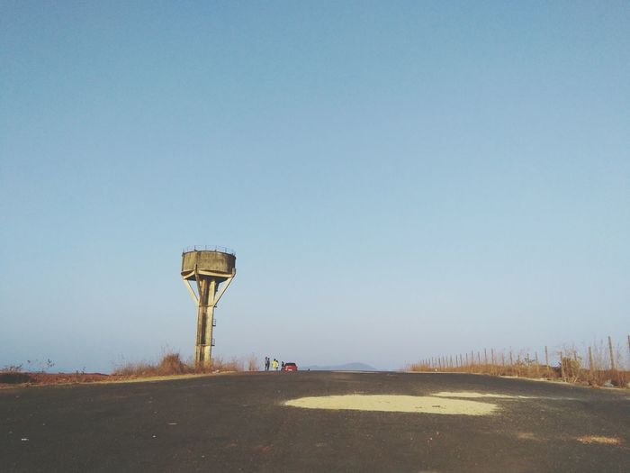 Water tower by road against clear sky