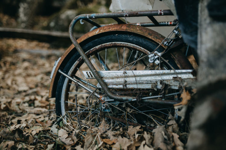 Close-up of abandoned bicycle on field