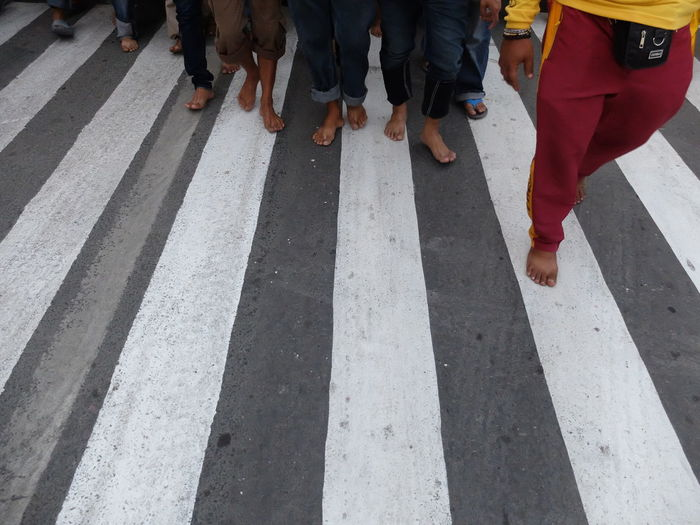 Low section of people walking on road marking