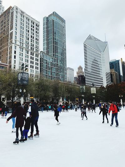 Building Exterior Cold Temperature Built Structure Winter City Snow Group Of People Ice Office Building Exterior Large Group Of People Winter Sport Ice-skating Architecture Crowd Real People Leisure Activity City Life Building Men Tall - High