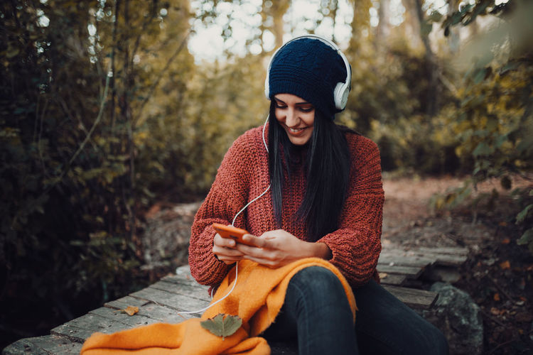 Young woman listening music while using smart phone in forest