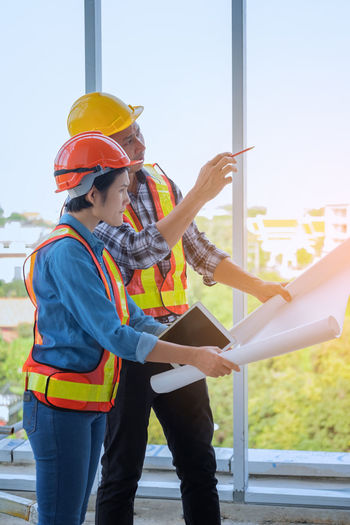 Coworkers Holding Blueprint While Working At Construction Site