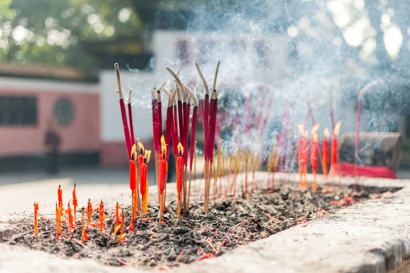 Close-up of lit candles and incense outdoors