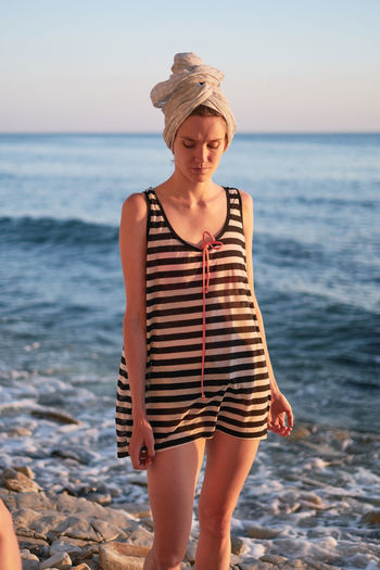 Young woman with head wrapped in towel standing at beach