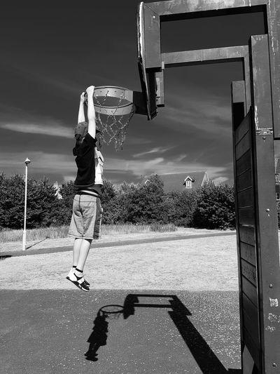Boy hanging on basketball hoop against sky